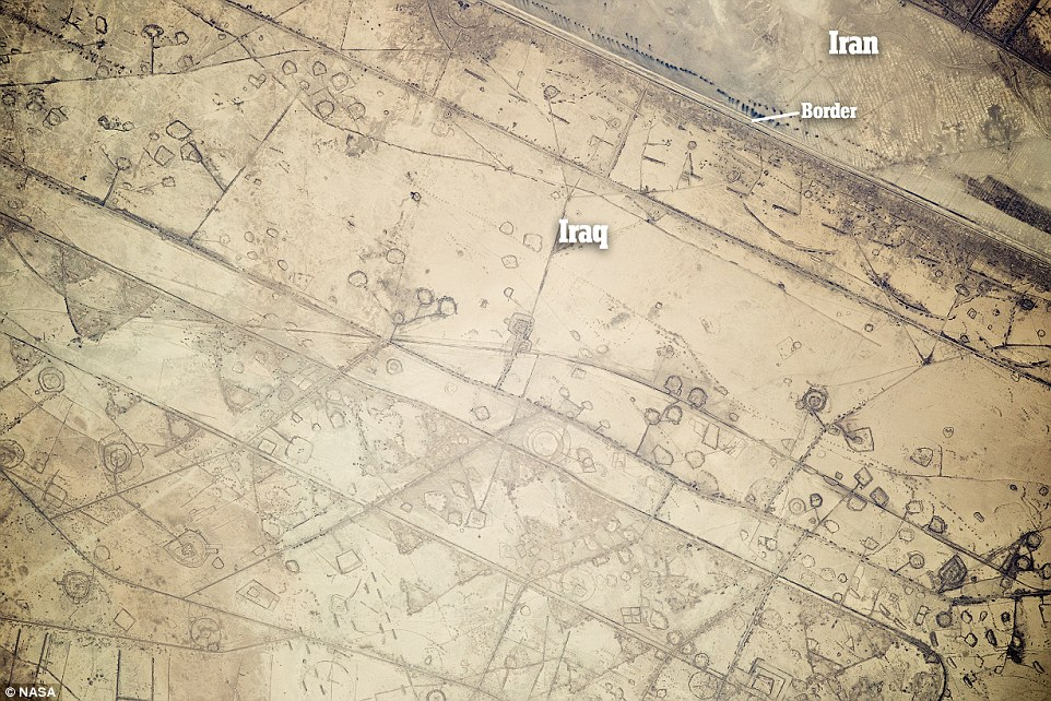 An image taken aboard the International Space Station has revealed remnants of war at the Iran-Iraq border, shown. In the image Iran is at the top right, the border between the countries is the line below the blue dots and Iraq is to the south